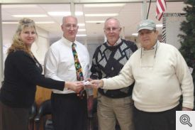 Mountain Pine High School Administrative Assistant Shannon Currington and School Counselor Paul Simms accept a check from Knights of Columbus fundraiser co-chairs Bill Roe and Mike Welsh.