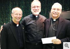Pictured (l-r) following the presentation of the check: Father Bill Elser, Monsignor Scott Friend, and Bishop Anthony Taylor.