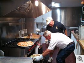 Scott Kantz and Dan Murphy heating the pizzas in the St Francis kitchen.